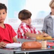 Little boy sighing in a classroom - Stock Photo