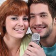 Young couple with a microphone — Stock Photo #8555667