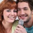 Young couple with a microphone - Stock Photo