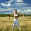 Woman practicing yoga in a field — Stock Photo