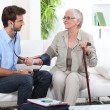 Young man taking the blood pressure of an older lady — Stock Photo #8555962