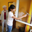 Stock Photo: Young woman helping senior woman doing chores