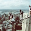 Climbers on a rope with cityscape in the background, photomontage - Stock Photo