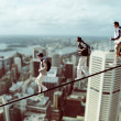 Stock Photo: Climbers on a rope with cityscape in the background, photomontage