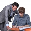 Teacher helping student with his studies — Stockfoto #8556243