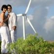Stock Photo: Couple stood by wind farm