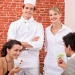 Stock Photo: A couple dining at restaurant, a cook and a waitress behind them
