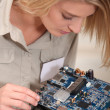 Female computer technician holding circuit board — Stock Photo