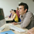 Stock Photo: Young man using a computer in class