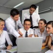 Business team gathered around laptop — Stock Photo