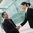 Photo: Executives shaking hands outside an office building