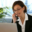 Woman on the phone at her desk — Stock Photo