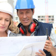 Construction worker looking at an engineer's drawing — Stock Photo