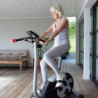 Elderly woman on an exercise machine — 图库照片