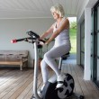 Elderly woman on an exercise machine — ストック写真