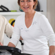 Mature woman using an exercise machine — Stock Photo