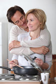 Man hugging a woman cooking at an electric stove — Stock Photo