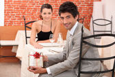 Couple dining in a romantic restaurant, the man is showing a present — Stock Photo