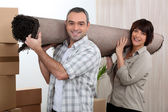 Couple carrying carpet over shoulders — Stock Photo