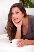 彼女のリビング ルームでのコーヒーのカップを飲む女性 — ストック写真