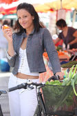 Woman eating a clementine while standing with her bike at a market — Stock Photo