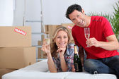 Couple holding champagne glasses boxes in background — Stock Photo