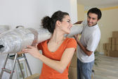 Couple carrying new rolled-up carpet in to house — Stock Photo
