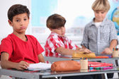 Little boy sighing in a classroom — Stock Photo