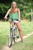 Young woman on a bike in the countryside — Stock Photo