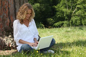 Woman laughing at her laptop computer in the park — Stock Photo