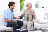 Young man taking the blood pressure of an older lady — Stock Photo