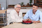 Young man playing with senior woman — Stock Photo