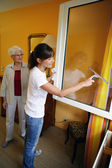 Young woman helping senior woman doing chores — Stock Photo