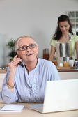 Elderly woman on the phone and surfing the internet — Foto Stock