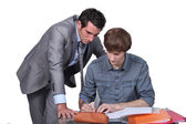 Teacher helping a student with his studies — Stockfoto