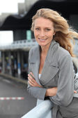 Blond woman leaning against railing outside building — Stock Photo