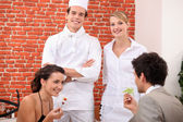 A couple dining at restaurant, a cook and a waitress behind them — Stock Photo