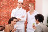 Pár stolování v restauraci, kuchaře a servírku za nimi — Stock fotografie