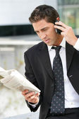 Businessman with phone and newspaper — Stock Photo