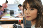 Young woman in a busy office — Stock Photo