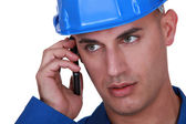 Man with a hardhat and cellphone — Stock Photo
