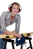 Female carpenter wearing protective muffs — Stock Photo