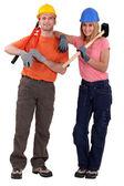 Uma equipe de trabalhadores segurando ferramentas em seus ombros — Fotografia Stock