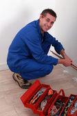 Plumber kneeling by tool box — Stock Photo