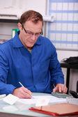Uomo, usando la calcolatrice per verificare i conti — Foto Stock