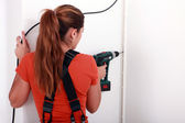 Woman drilling into wall — Stock Photo