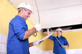 Two electricians in a room under construction — Stock Photo