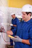 Två män kontroll strömförsörjning — Stockfoto