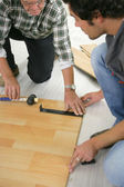 Father and son installing wooden flooring — Stock Photo