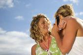 Dvě blonďaté přátelé volání, zatímco na pláži — Stock fotografie